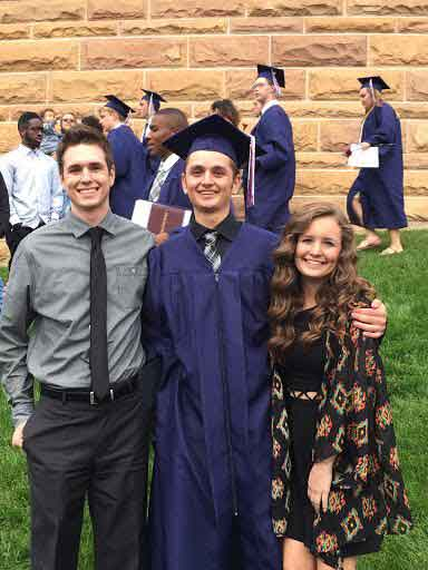 Senior Madi Koenig poses with her two older brothers after graduation.