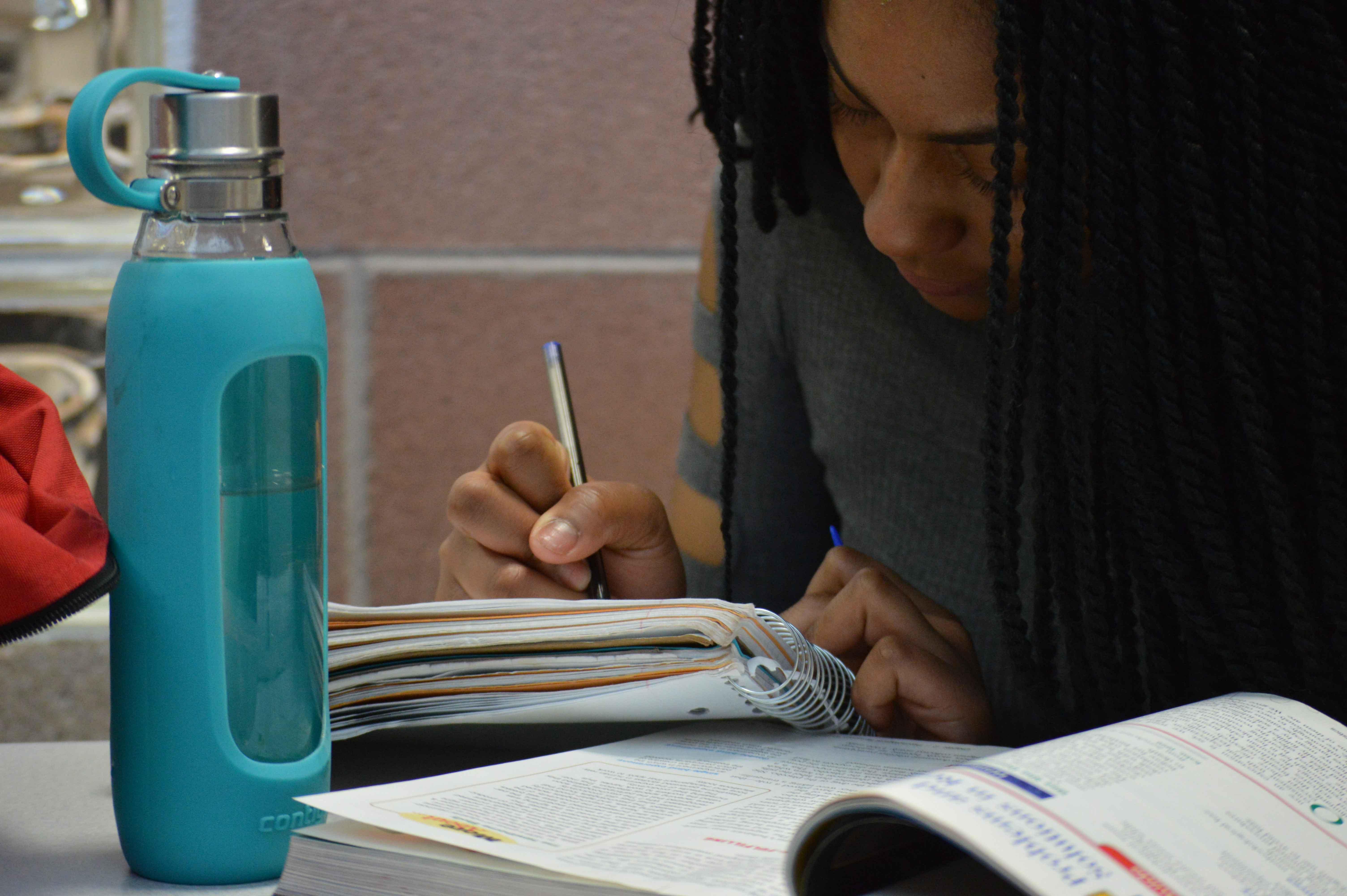 Head bent over her psychology homework, Keyana Pollard works in the science hall.