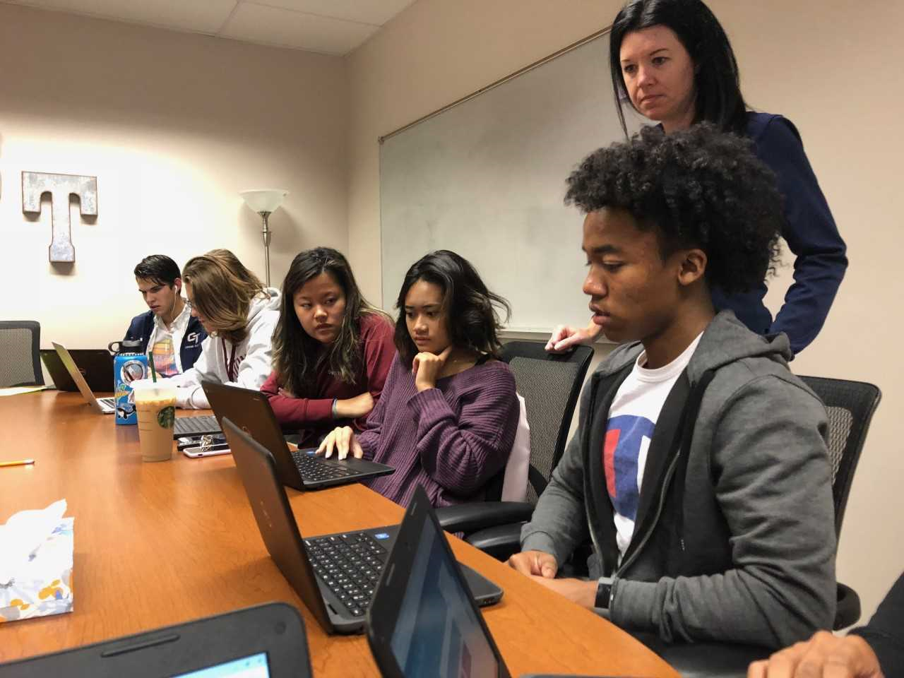 In a college application workshop, Ms. Gillespie assists seniors in matching their common application in Naviance.