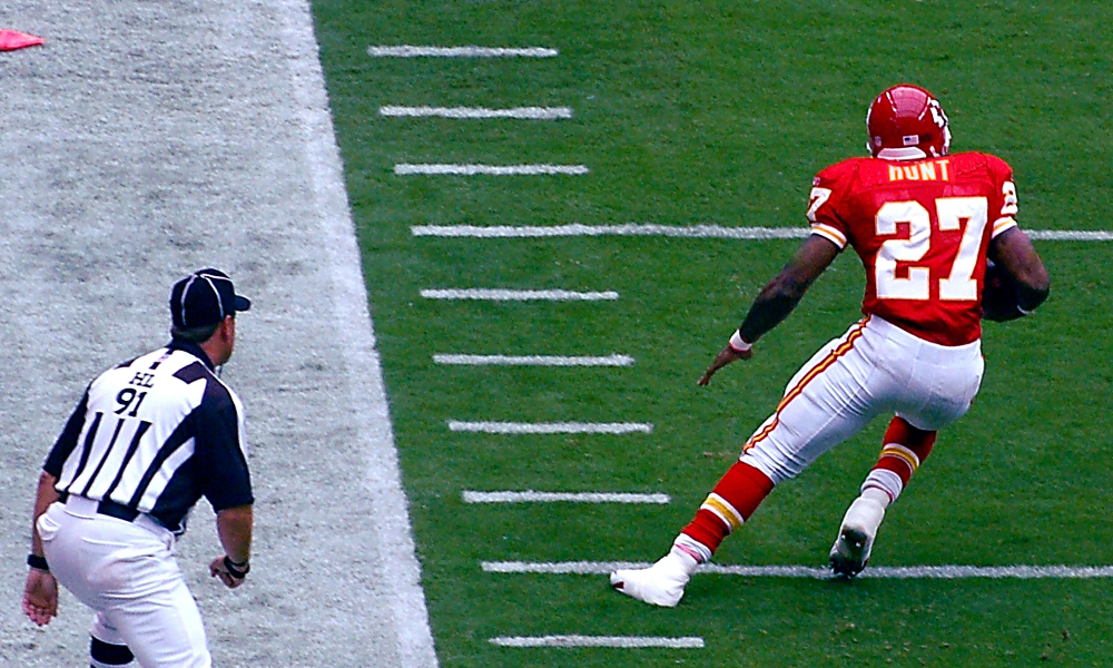 In action, former chiefs player Kareem Hunt attempts to run the ball for a touchdown with a close eye on him, during the 2017 football season. Photo obtained through: Public Domain 1.0