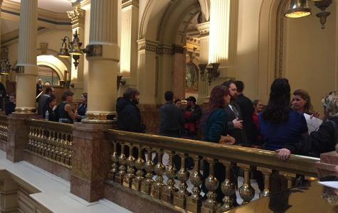"Lines of people stand around or leaned up against the gold fixtures and towering walls present on the second floor of Colorado's Capitol building. On Jan. 30, 2019 over 300 witnesses came forth with their opinions of Health Bill 19-1032 in order to influence the decision of its passage. Bente Birkland of Colorado Public Radio in her article ""Colorado Comprehensive Sex Ed Bill Advances After Combative, Explicit Testimony"" called it, ""The biggest hearing of the 2019 legislative session to date…"". The committee voted 7-4 in support of the bill, progressing it to the next step in the legislative process."
