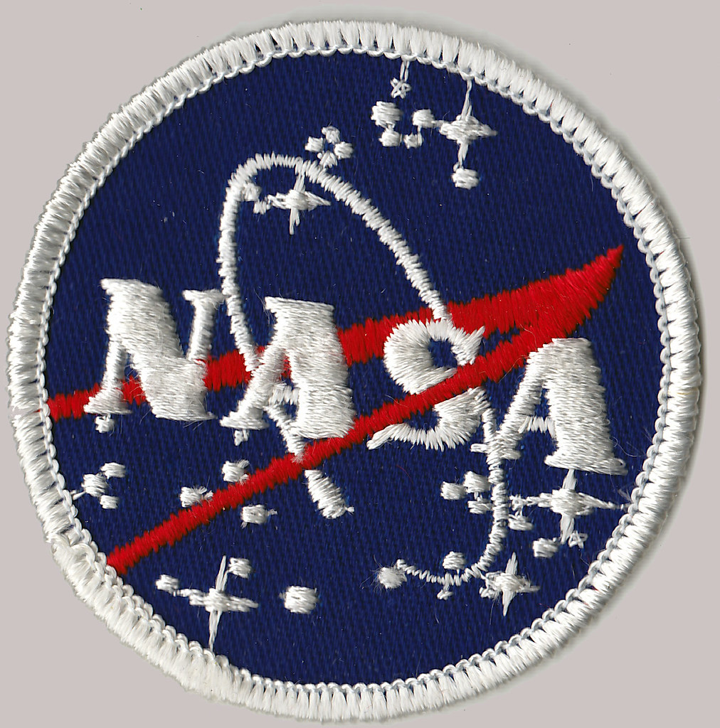 The NASA badge glints, illuminating the bold red and blue threads of the nation's premiere space exploration agency's emblem. The patriotic colors of the logo are emphasized after the first all female space walk.