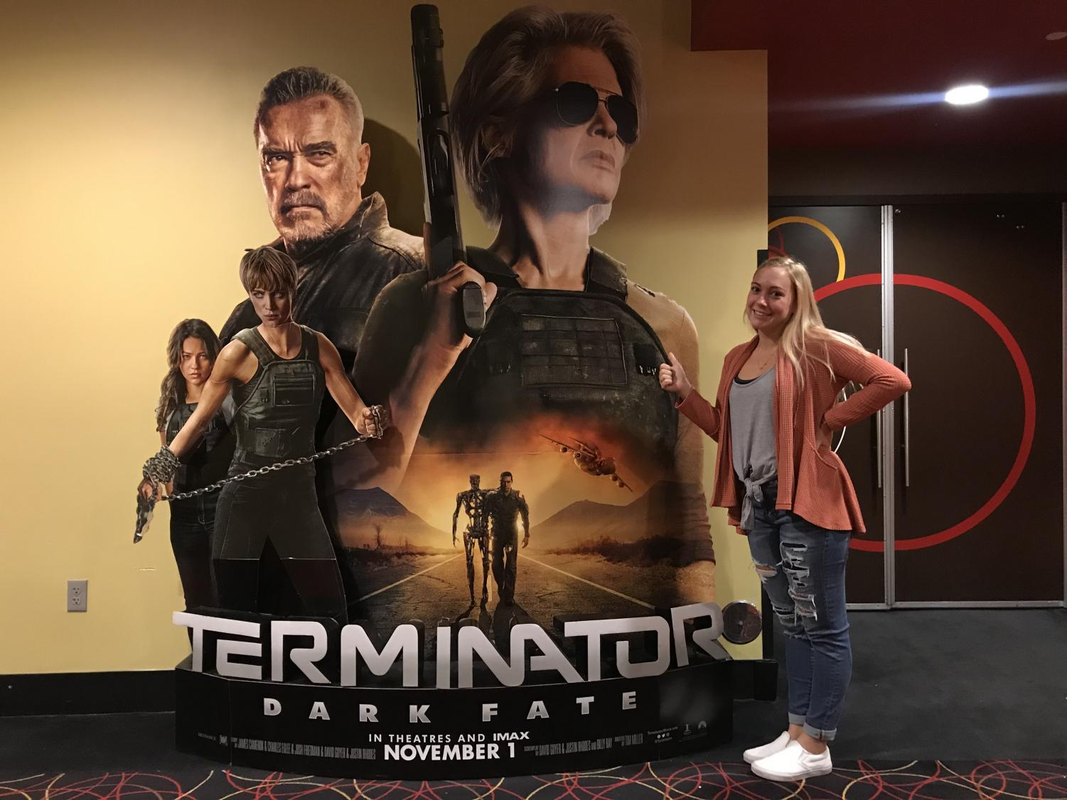 Grinning in front of a large Terminator poster, Managing Editor Elyse Sommer grins after watching the new Terminator: Dark Fate movie on November 3, the day after the newest terminator film's debut.  The film, featuring Arnold Schwarzenegger and Linda Hamilton, is a textbook box office flop, grossing $123 million in its budget of $185-$195 million, even if viewers like Sommer enjoyed the movie for all the gory, gruesome ways it is exactly like its predecessors. Photo courtesy of Dan Sommer.