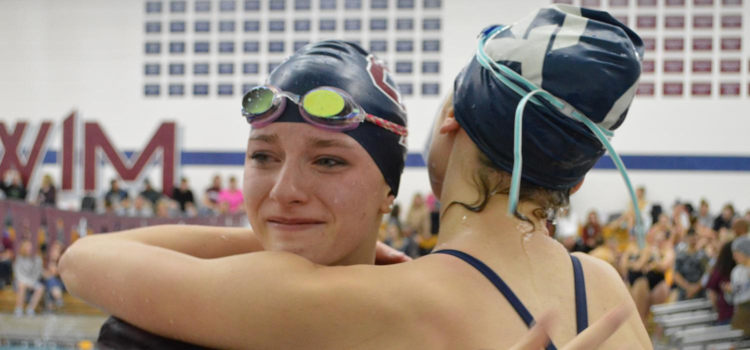 "Happy Tears:  Skylar Brogch (10) cries in the arms of a teammate after having swam an incredible time against Mullen on December 12.  In the meet against Mullen, Brogch clocked in a time for the 100 fly that was a mere 0.6 seconds away from the pool's record.  ""After having worked so hard, it just feels amazing,"" said Brogch of the immense accomplishment. Brogch has already qualified for the State meet in both the 200 free and 100 fly races after only a handful of meets."