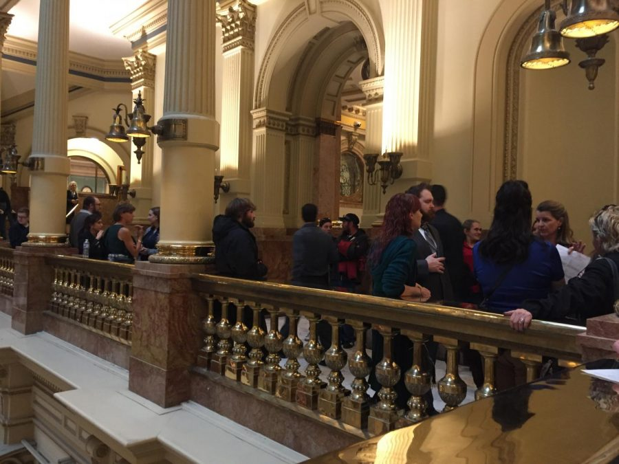 """Lines of people stand around or leaned up against the gold fixtures and towering walls present on the second floor of Colorado's Capitol building. On Jan. 30, 2019 over 300 witnesses came forth with their opinions of Health Bill 19-1032 in order to influence the decision of its passage. Bente Birkland of Colorado Public Radio in her article """"Colorado Comprehensive Sex Ed Bill Advances After Combative, Explicit Testimony"""" called it, """"The biggest hearing of the 2019 legislative session to date…"""". The committee voted 7-4 in support of the bill, progressing it to the next step in the legislative process."""