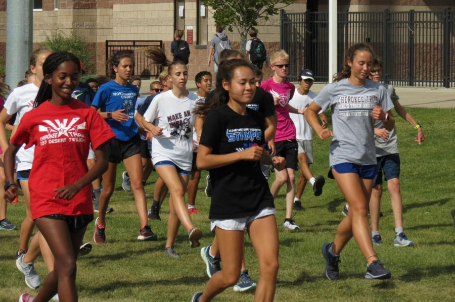 """Leading the pack. Soonhee Han (12) leads the Cross Country team through a warm up during practice on August 26, 2019. Han explained that an important part of being a leader is """"...setting a good example and doing what's right because the freshman...look up a lot to see what to do…"""" Han, like many other leaders in the school, aims to add to the community through helping others within their sport or club."""