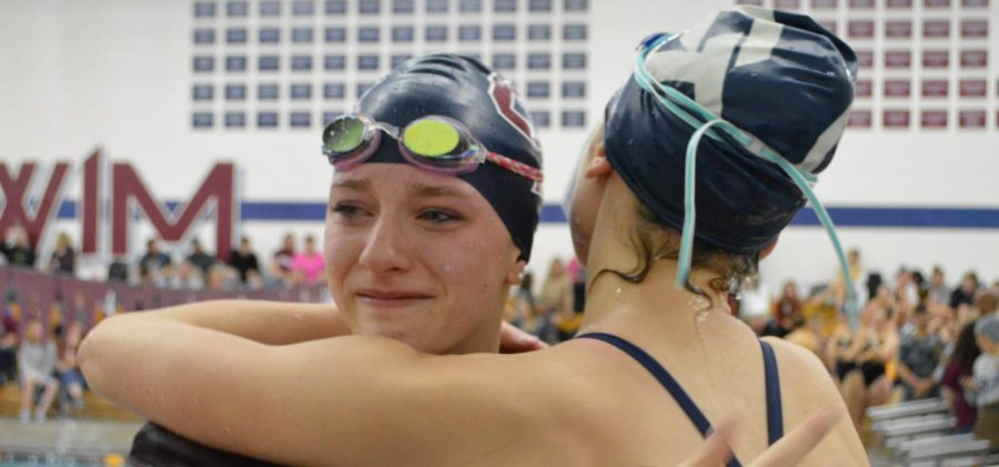 """Happy Tears:  Skylar Brogch (10) cries in the arms of a teammate after having swam an incredible time against Mullen on December 12.  In the meet against Mullen, Brogch clocked in a time for the 100 fly that was a mere 0.6 seconds away from the pool's record.  """"After having worked so hard, it just feels amazing,"""" said Brogch of the immense accomplishment. Brogch has already qualified for the State meet in both the 200 free and 100 fly races after only a handful of meets."""