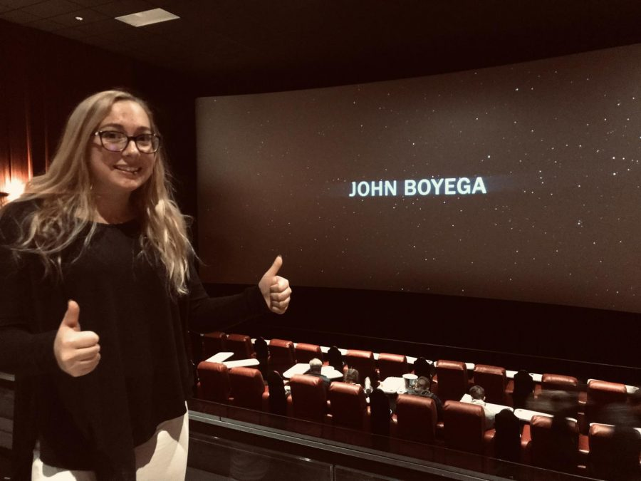 Grinning in front of the credits after the newest Star Wars installment, Rise of Skywalker, Elyse Sommer flashes a double thumbs up, a hallmark of her movie review approval.  John Boyega starred alongside Daisy Ridley and Adam Driver in the final film in the franchise, hopefully, that grossed nearly $150 million in its first day.  Photo courtesy of Dan Sommer.