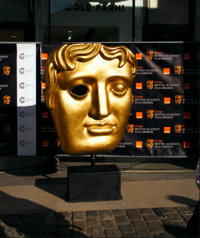 A classic BAFTAs mask in traditional large style appears on a red carpet. The BAFTAs, standing for British Academy for Film and Television Arts, are held in early February, before the Oscars. This year, the nominees are suspiciously Caucasian and male, a discriminatory lineup that is not tolerated by Hollywood's elite. Photo courtesy of Chloe (CC BY 2.0)