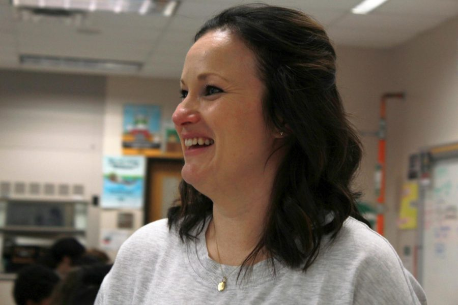 While speaking with a student, Ms. Julie Scheffel smiles and laughs.