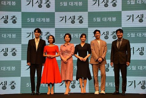 The cast of Parasite stands for a photo op at a press event. From left to right: Choi Woo-shik, Cho Yeo-jeong, Lee Jung-eun, Park So-dam, Lee Sun-kyun and Song Kang-ho.