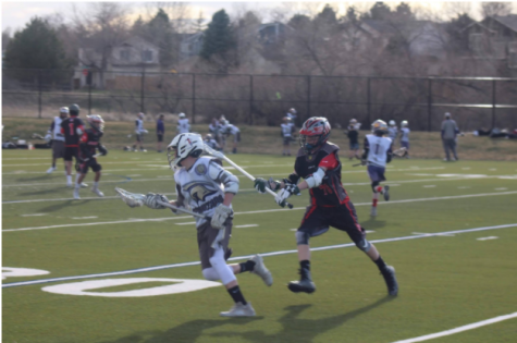 """C.J. Vigil, a sophomore playing lacrosse on a chilly fall day.  C.J has always loved lacrosse and this passion is what drives him to play for Cherokee Trail,  """" My favorite thing about lacrosse is definitely teamwork,""""  explained Vigil.  Teamwork is one of the main reasons sports are popular and why fans like to cheer them on.    Photo Credit unknown"""